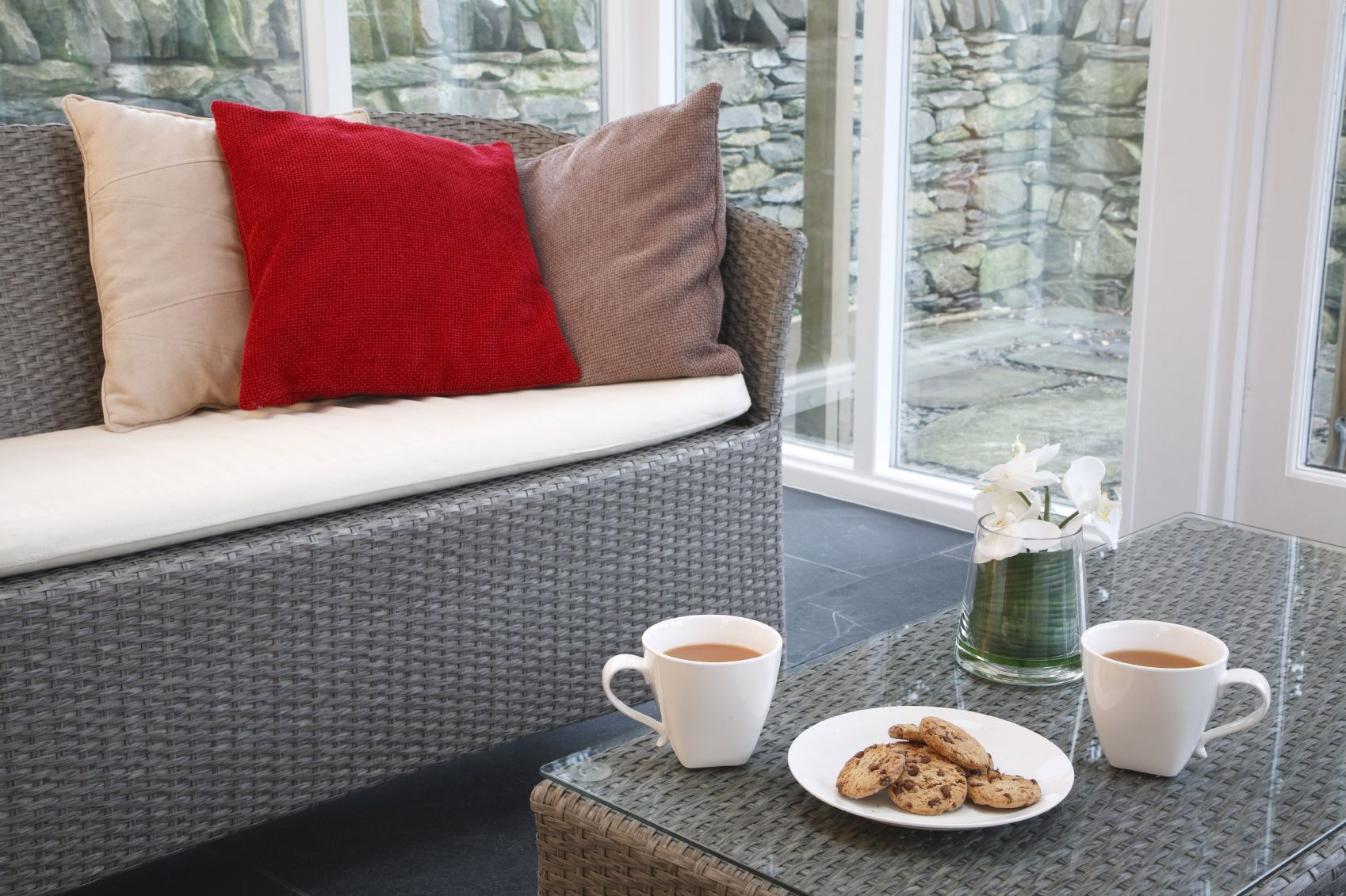 Conservatory interior design with rattan chairs and coffee table