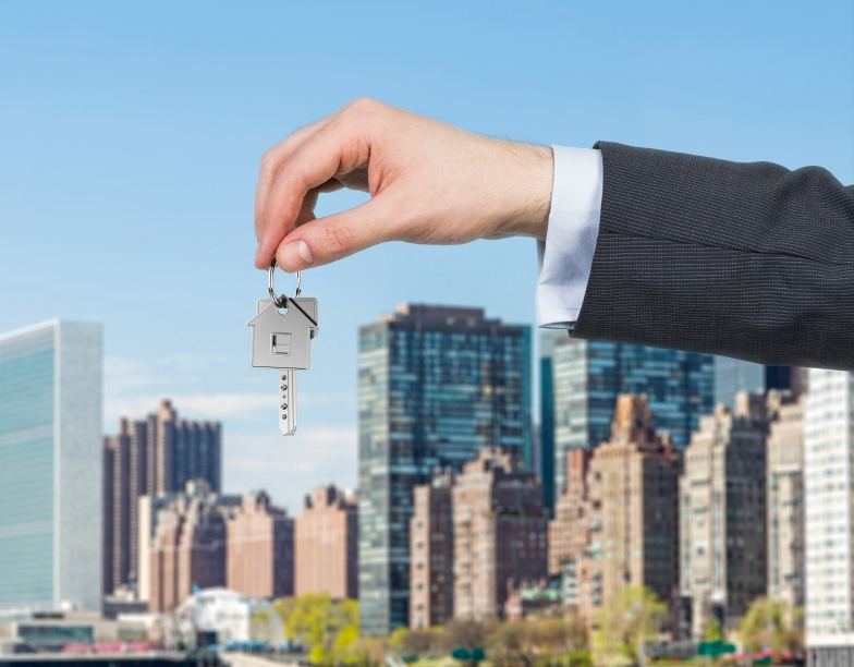 hand holding keys in front of city backdrop